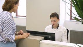 Männlicher Angestellter spricht auf Frau des Telefons dann sich nähert ihm im Büro stock video