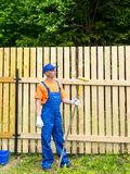 Männlicher Arbeiter, der nahe dem Bretterzaun stillsteht Lizenzfreies Stockfoto