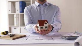 Männlicher Architekt mit Hausmodell und -plan stock video