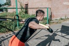 Männlicher Athlet, ausgepreßt heraus auf Schleifen, Ausbildungsbügel, im Sommer in der Stadt auf dem Sportfeld Aktives Training,  lizenzfreies stockbild
