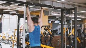 Männlicher Athlet - das Bodybuilderhandeln zieht Abdominal- Übung der Stange in der Turnhalle hoch Lizenzfreie Stockfotos