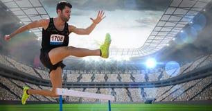 Männlicher Athlet, der über die Hürde im Stadion springt stockbild