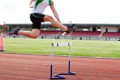 Männlicher Athlet, der über eine Hecke während eines Rennens springt stockbild
