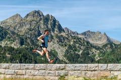Männlicher Athlet, der über eine Steinwand in den Bergen läuft lizenzfreies stockbild