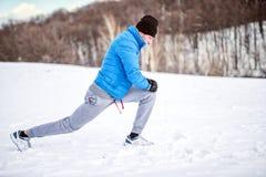 Männlicher Athlet, der auf Schnee ausdehnt Lizenzfreies Stockfoto