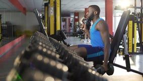 Männlicher Athlet, der mit Dummköpfen in der Turnhalle, aktiver gesunder Lebensstil, Eignung trainiert stock footage