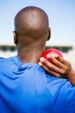 Männlicher Athlet, der sich vorbereitet, Kugelstoßenball zu werfen Stockfotografie