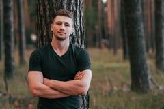 Männlicher Athlet, der zurück im Holz auf einem Hintergrund eines Baums hinter seinem aufwirft Aktive Lebensstileignung, Training lizenzfreie stockfotos