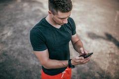 Männlicher Athlet, Sommer auf Sportfeld in seinem Handsmartphone schreibt Mitteilung zum Internet, Anwendung für Impulstraining stockbilder
