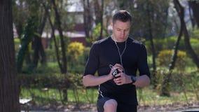 Männlicher athletischer Rüttler hört zu laufen auf, um das Gegen smartwatch zu gründen und seinen Smartphone zu überprüfen stock footage