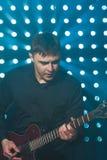 Männlicher auf Gitarre spielender und singender Musiker Stockfotos