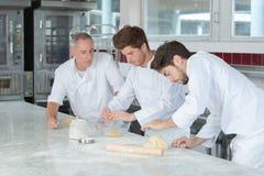 Männlicher Bäcker und Assistenten stockfotografie