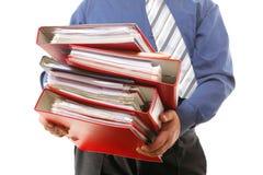 Männlicher Büroangestellter, der einen Stapel Dateien trägt Stockfotografie
