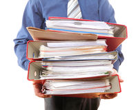 Männlicher Büroangestellter, der einen Stapel Dateien trägt Lizenzfreie Stockfotos