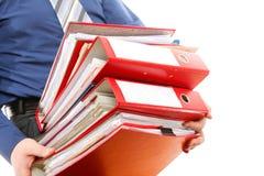 Männlicher Büroangestellter, der einen Stapel Dateien trägt Stockfotos