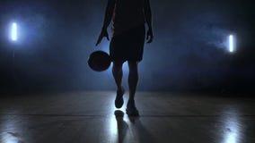Männlicher Basketball-Spieler, der in den Rauch an der Kamera klopft den Ball über den Parkettboden in der Zeitlupe umzieht stock footage