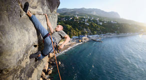 Männlicher Bergsteiger, der großen Flussstein in der Natur mit Seil klettert Lizenzfreies Stockfoto