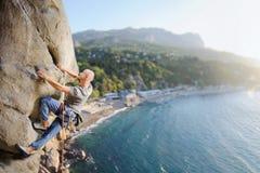 Männlicher Bergsteiger, der großen Flussstein in der Natur mit Seil klettert Lizenzfreie Stockfotos