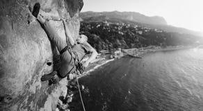 Männlicher Bergsteiger, der großen Flussstein in der Natur mit Seil klettert Stockfoto