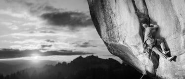 Männlicher Bergsteiger, der großen Flussstein in der Natur mit Seil klettert Lizenzfreie Stockbilder