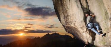 Männlicher Bergsteiger, der großen Flussstein in der Natur mit Seil klettert Stockfotos