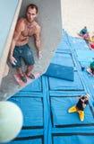 Männlicher Bergsteiger vor Sprung auf künstlichem Kletterwand Lizenzfreies Stockfoto