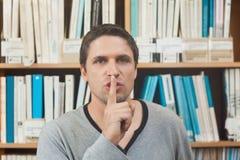 Männlicher Bibliothekar des Brunette, der Ruhe in der Bibliothek fordert Stockbild