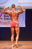 Männlicher Bodybuilder biegt seine Muskeln und zeigt seine beste Konstitution Stockbild