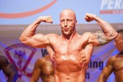 Männlicher Bodybuilder biegt seine Muskeln und zeigt seine beste Konstitution Lizenzfreies Stockbild
