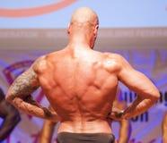 Männlicher Bodybuilder biegt seine Muskeln und zeigt seine beste Konstitution Lizenzfreies Stockfoto