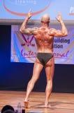 Männlicher Bodybuilder biegt seine Muskeln und zeigt seine beste Konstitution Stockfotografie