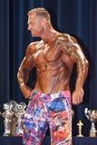 Männlicher Bodybuilder zeigt seine beste Kastenhaltung auf Stadium Lizenzfreie Stockfotografie