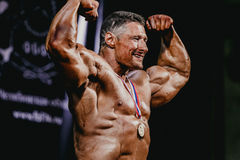 Männlicher Bodybuilder, zum von Wettbewerbshaltungen mit Medaille zu gewinnen Lizenzfreie Stockfotografie