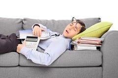 Männlicher Buchhalter, der auf einem Stapel von Ordnern schläft Stockfotografie