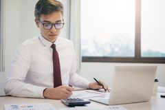 Männlicher Buchhalter oder Banker berechnen die Bargeldrechnung stockbilder