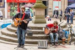 Männlicher Busker zwei, der Gitarren spielt und beim Lymelight Fes singt stockfotos