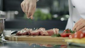 Männlicher Chef, der Fleisch an der Küche salzt Nahaufnahmechefhände, die Steak am Arbeitsplatz salzen stock video footage