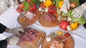 Männlicher Chef, der großes Stück Rindfleisch auf hölzernem Brett in der Restaurantküche schneidet Mannkoch, der Steak und Gemüse stock video footage