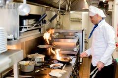 Männlicher Chef, der mit brennenden Flammen kocht lizenzfreies stockfoto