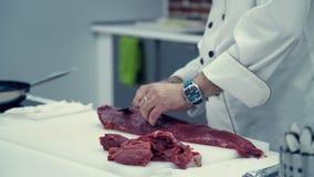 Männlicher Chef schneidet dünne Scheiben des Fleisches von einem Stück Rindfleisch stock video footage