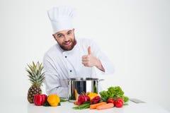Männlicher Chefkoch, der Lebensmittel zubereitet und sich Daumen zeigt Lizenzfreies Stockfoto
