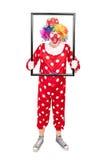 Männlicher Clown, der einen großen Bilderrahmen hält Stockbilder