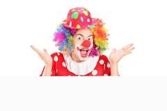 Männlicher Clown, der hinter Leerplatte gestikuliert Lizenzfreies Stockfoto