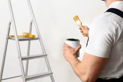 Männlicher Dekorateur mit Bürste und Farbe kann zuhause Raum für Text lizenzfreies stockbild
