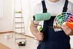 Männlicher Dekorateur mit Farbenrollen- und Farbpalettenproben im leeren Raum Raum für Text stockfotos