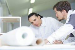 M?nnlicher Dekorateur und junge Frau, die zuhause Reparaturplan studiert stockbild