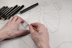 Männlicher Designer macht eine Ausführungszeichnung Arbeitsplatz eines Spielzeugdesigners Markierungen, Machthaber, Stift und Ble lizenzfreie stockfotos