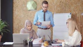 Männlicher Direktor erklärt seine zwei weiblichen Angestellten im Büro stock video