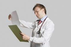 Männlicher Doktor in den Laborkittellesekrankenblättern über grauem Hintergrund Stockfoto