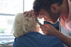 Männlicher Doktor, der älteres weibliches geduldiges Ohr mit Otoscope überprüft stockbild